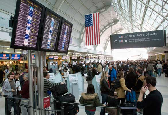 Passengers bound for the U.S. wait to go through customs at Toronto International Airport.  (Frank Gunn / Canadian Press)