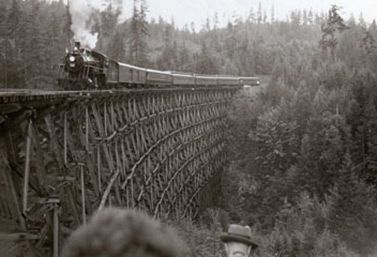 A steam locomotive crossing a massive wooden bridge in turn-of-the-century British Columbia (Library and Archives Canada)