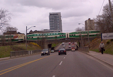 An afternoon GO Train runs through a Toronto suburb in April (Joe Fiorino/CBC)