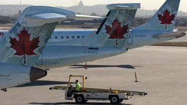 Aviones de Air Canada esperan en su puerta de embarque respectiva en el aeropuerto internacional de Montreal, el tercero en importancia de Canadá. Se percibe en el fondo la silueta de la montaña Mont-Royal, detrás de la cual se encuentra el centro de la ciudad de Montreal.   (Ryan Remiorz/Canadian Press)