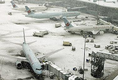 Aviones de Air Canada, cubiertos de nieve, esperan la señal para hacer abordar los pasajeros, en Toronto.   (Richard Lam/Canadian Press)