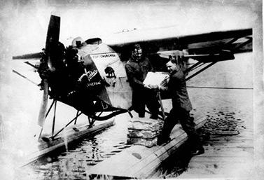Un aviador entrega el correo a su colega Fred Stevenson, en 1927. (Archives de l'aéroport international de Winnipeg)