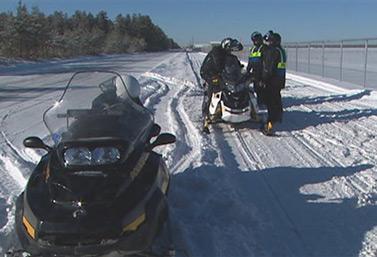 Una pista de motos de nieve en Quebec, con motivo de la Semana Internacional de la Seguridad de este tipo de vehículos. Se puede ver a los agentes del orden que entregan un papel de instrucciones a los conductores de las motos de nieve. (Radio-Canada)