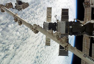 El 13 de agosto del 2007, el astronauta canadiense Dave Williams, sujetado por el brazo espacial canadiense* mientras efectúa trabajos de mantenimiento de la Estación Espacial Internacional. (*También llamado Canadarm o SRMS, Servicio Remoto del Sistema Manipulador. Es un brazo mecánico)