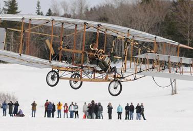 Une réplique du Silver Dart s'élance dans le ciel le jour du 100e anniversaire du premier vol d'avion au Canada. (CBC News)