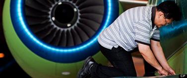 Un travailleur assemble une des pièces d'un avion d'affaires de fabrication canadienne dans un hangar de la compagnie Bombardier, à Toronto. (Presse Canadienne/Michelle Siu)