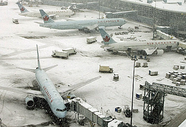 Des avions d'Air Canada, couverts de neige, attendent le signal pour faire monter leurs passagers à bord, à Toronto. (Richard Lam/Canadian Press)