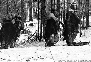 Des Indiens micmacs se promènent dans une forêt, l'hiver, dans l'est du Canada. Cette photo a été prise en 1981, lors du tournage d'un documentaire historique de la télévision de CBC. (Musée de la Nouvelle-Écosse)