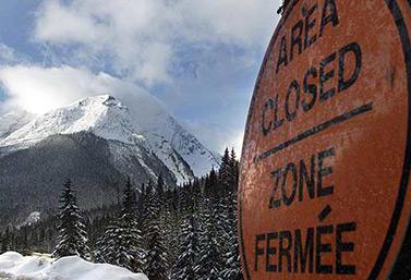 Une enseigne dans le parc national Glacier, en Colombie-Britannique, avertit les promeneurs que le sentier est fermé en raison d'une avalanche qui a emporté sept adolescents quelques heures plus tôt. (Adrian Wyld/Canadian Press)