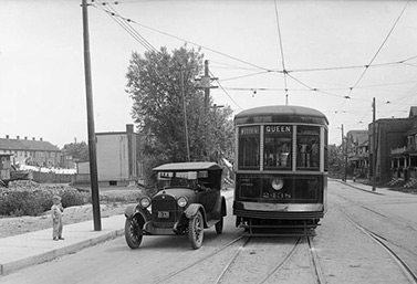 Dans les années 1920, à Toronto, une automobile et un tramway partagent la voie à l'angle des rues Queen et Bay. (Archives publiques, Ville de Toronto)
