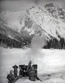 Une photo des années 1960 où on voit des militaires déclencher une avalanche le long de l'autoroute Transcanadienne. (Parc Canada)