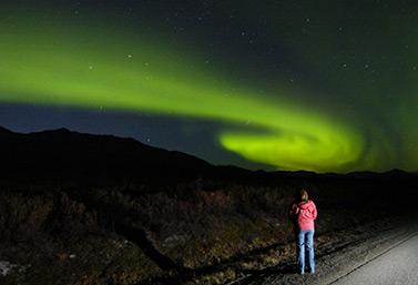 Une femme contemple une aurore boréale pendant une belle nuit du mois d'août 2010. (M. Scott Moon/Canadian)