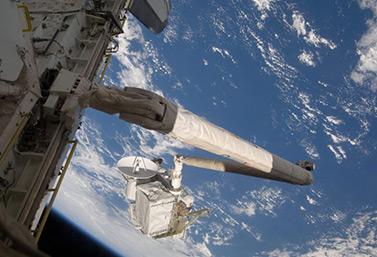 Sur cette photo prise le 21 juillet 2009, la navette spatiale Endeavour déploie le bras canadien de deuxième génération. (Canadian Press/NASA)