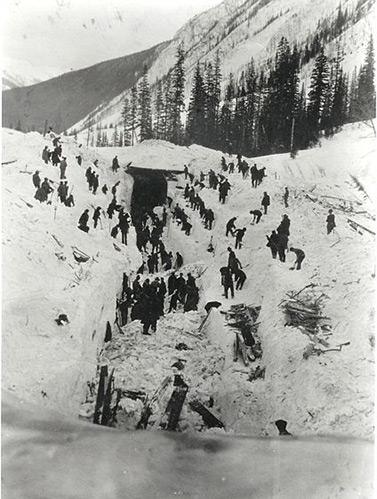 Le 5 mars 1910, des employés du chemin de fer transcanadien tentent de dégager la voie et de déterrer les corps de malheureux emportés un jour plus tôt par une avalanche. (Musée Revelstoke)