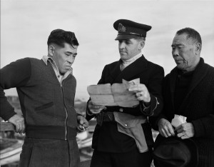 Esquimault, British Columbia; December 9,1941--Internment Camps--R.C.N. officer questioning Japanese Canadian fishermen while confiscating their boat, Esquimault, British Columbia, 9 December 1941(CP PHOTO) 1999 (National Archives of Canada) PA-112539