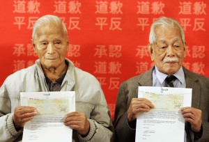 Thomas Soon (left) 97-years-old and Charlie Quon, 99-years-old, hold government cheques, the first redress payments to Chinese Head Tax payers in Vancouver Friday October 20, 2006. (CP P HOTO/Lyle Stafford)