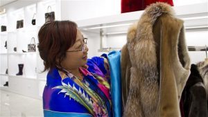 Dans le magasin Always in Vogue de Shenyang, une cliente examine un manteau en peau de phoque. PHOTO : ICI RADIO-CANADA/PHILIPPE GRENIER