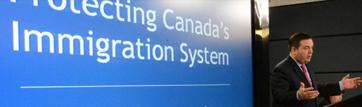 un homme devant un grand écran sur lequel est écrit le texte «Protecting Canada's Immigration System»
