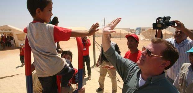 Le ministre canadien des Affaires étrangères John Baird accueille un réfugié syrien garçon s au camp de réfugiés de Zaatari, à Mafraq, Jordanie, samedi. (Mohammad Hannon / Associated Press)