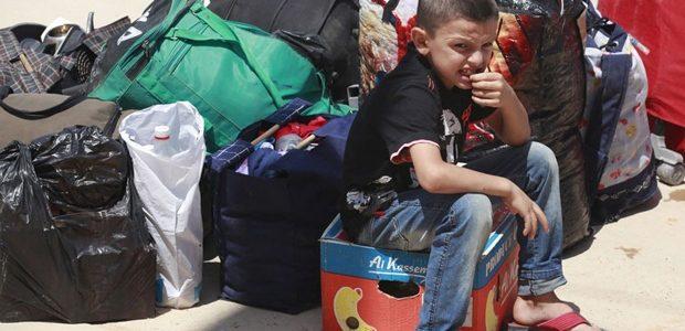 Un jeune garçon réfugié syrien est assis à côté de sacs à son arrivée au poste frontière de la ville irakienne de Qaim, à 320 kilomètres à l'ouest de Bagdad, en Irak. (Hadi Mizban / Associated Press)