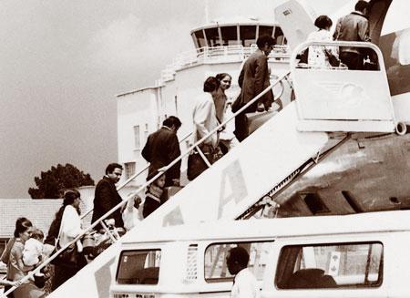 Des immigrants asiatiques montent à destination du Canada à bord d'un avion en Ouganda, 1972 à l'aéroport d'Entebbe. Wikipédia