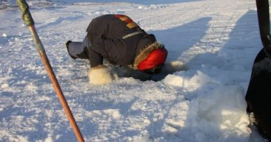 An Inuit hunter peers into a hole in the ice to check his fishing nets. Photo by Levon Sevunts.