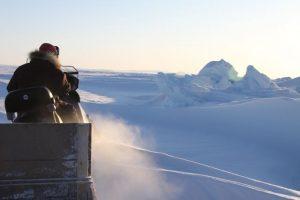 Elijah Pallituq, chasseur et guide inuit, conduit sa motoneige sur la mer glacée près de Clyde River, au Nunavut. Photo Levon Sevunts.