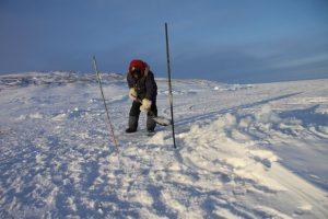 Un chasseur inuit utilise une pelle pour recouvrer un trou dans la neige Photo Levon Sevunts.