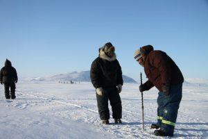 Des chasseurs inuits arpentent les fissures dans la glace afin de trouver un endroit approprié où tendre leurs filets. Photo Levon Sevunts.
