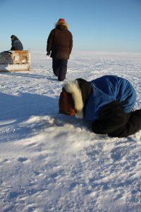 Un jeune chasseur inuit regarde dans un trou d'air qu'utilisent les phoques pour respirer sous la mer glacée près de Clyde River, au Nunavut. Photo Levon Sevunts.