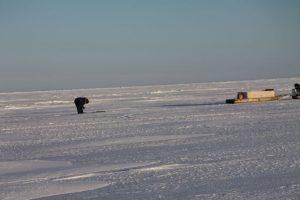 Un chasseur inuit se tient debout au-dessus d'un trou d'air sur la mer glacée. Photo Levon Sevunts.