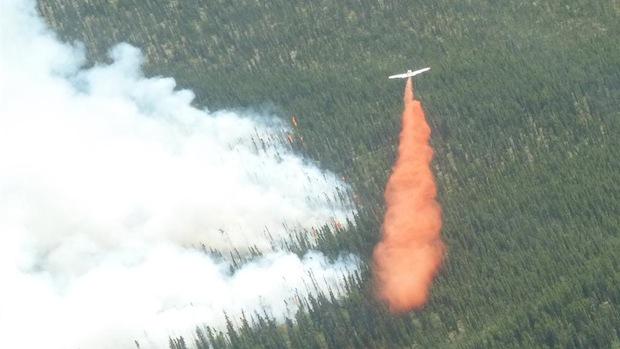 Un avion-citerne déverse sa cargaison de liquide ignifuge près d'un brasier au Yukon.  (Yukon Wildland Fire management)