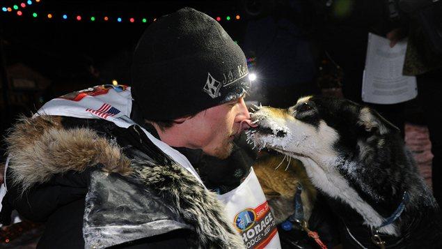 Moment de tendresse entre le vainqueur de la course Iditarod, Dallas Seavey et un des ses chiens au fil d'arrivé. (Bob Hallinen/Anchorage Daily News/La Presse Canadienne)