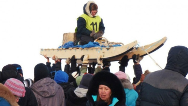 The crowd hoists up one of the mushers in the 2013 Nunavut Quest race from Arctic Bay to Igloolik. (Photo courtesy of Angela Coxon)