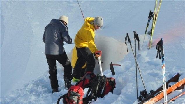 Une équipe de l'Association des avalanches du Yukon examine le manteau de neige afin de déterminer les risques d'avalanches. (Philippe Morin/Radio-Canada)