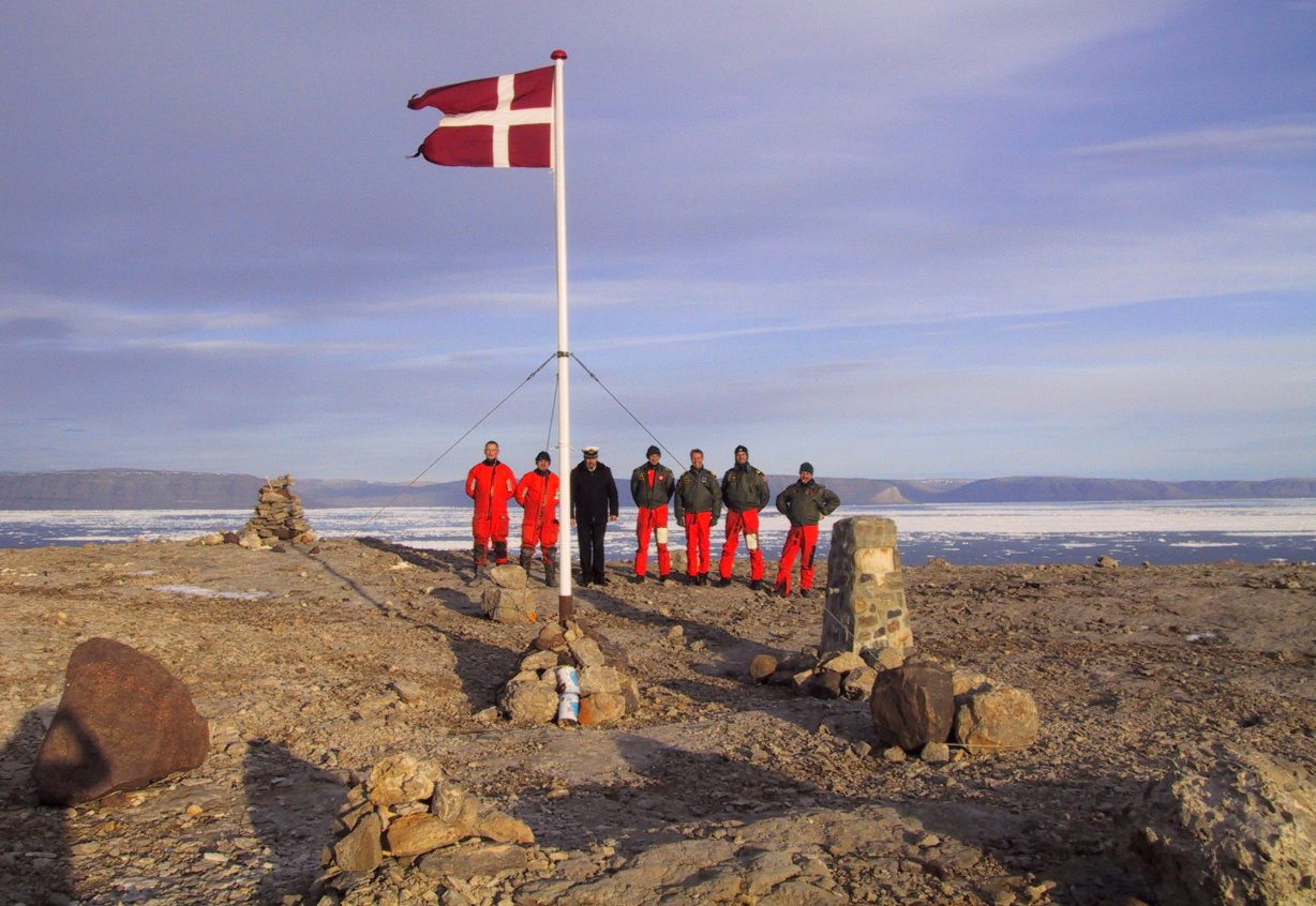 The crew of Danish warship Vedderen perform a flag raising ceremony on the uninhabitated Hans Island off northwestern Greenland, in this Aug. 13, 2002 file photo. Arctic experts from Canada and Denmark are proposing a novel solution to who controls an ice-bound speck of an island midway between the two countries.They say turn Hans Island into a condominium. (Polfoto, Vedderen/AP/The Canadian Press)