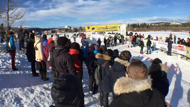 L'attente au soleil à la ligne d'arrivée du Yukon Quest. (Claudiane Samson/ICI Radio-Canada)