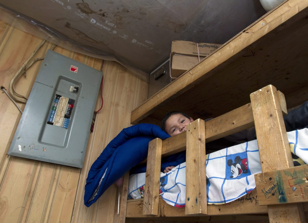 Seven-year-old Ferlin Lahtal lies in his home-made bunk bed in his home in Attawapiskat, Ontario Saturday December 17, 2011. Twenty-one people live in the house that has plastic on the ceilings to stop water entry. FRANK GUNN/THE CANADIAN PRESS