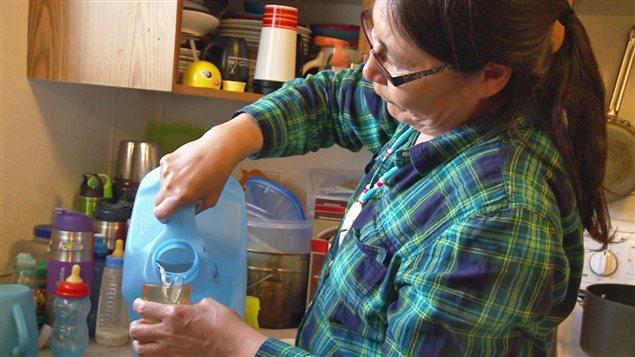 Maggie Sakanee, membre de la Première Nation Neskantaga, se verse un verre d'eau. Sa communauté ontarienne est sous un avis de faire bouillir l'eau depuis plus de 20 ans. (Martine Laberge/ICI Radio-Canada)