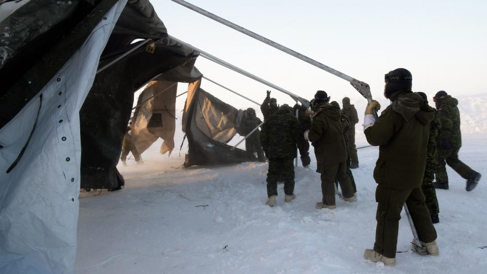 Les membres déployés du 12e Régiment blindé du Canada installent une tente modulaire en plein vent à Hall Beach, au Nunavut, le 22 février 2017. (Belinda Groves/ Forces armées canadiennes)