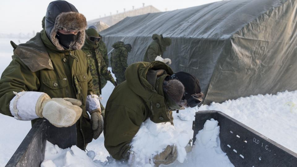 Les membres déployés du 12e Régiment blindé du Canada ramassent de la neige pour solidifier des tentes modulaires à Hall Beach, au Nunavut, le 22 février 2017. (Sgt Jean-François Lauzé/Forces armées canadiennes)