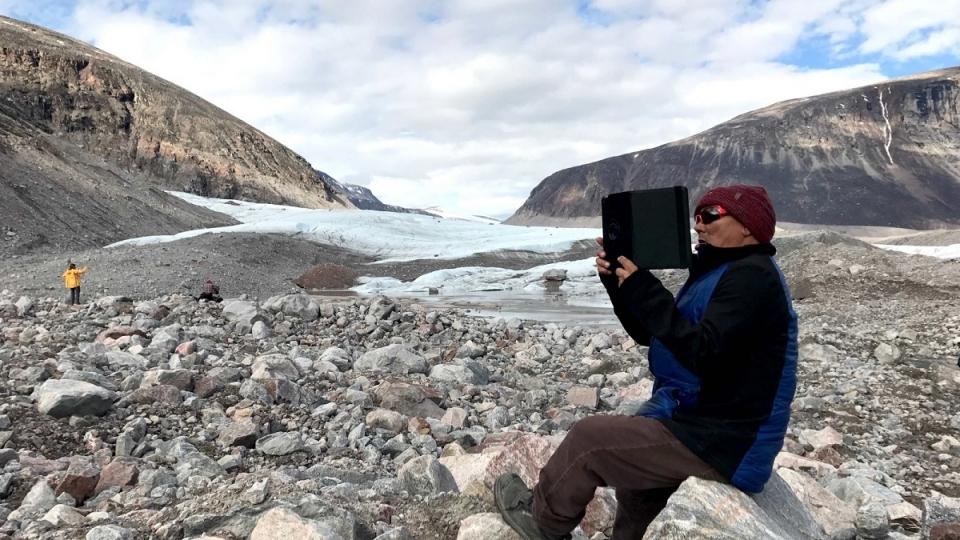 Sam Palituq prend le glacier en photo dans le fjord de Sam Ford, près des montagnes où il est né. (Marie-Laure Josselin/Radio-Canada)