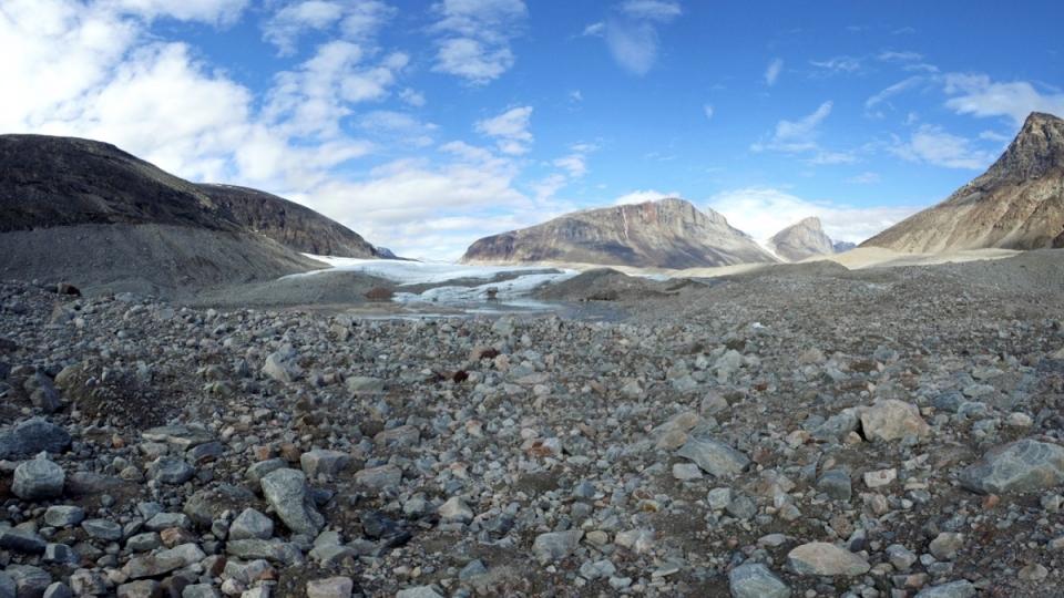 Sur ce glacier situé dans le fjord Sam Ford, on peut voir les moraines, cet amas de roches entraînées par le mouvement du glacier. En regardant les falaises, on peut imaginer la taille du glacier avant. La ligne est encore bien visible, séparant les falaises entre le clair et le foncé. Le glacier remplissait toute la vallée. (Marie-Laure Josselin/Radio-Canada)