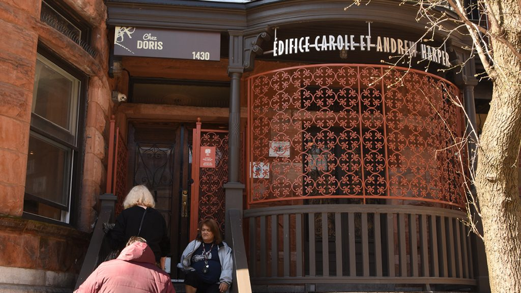 Quelques femmes montent l'escalier devant l'édifice de Chez Doris, qui arbore également un panneau indiqué Édifice Carole et Andrew Harper.